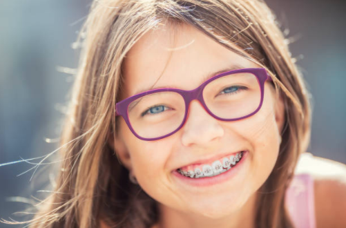 Girl with brown hair and glasses smiling with braces