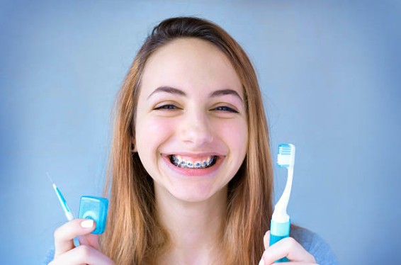 Girl with braces holding floss and toothbrush